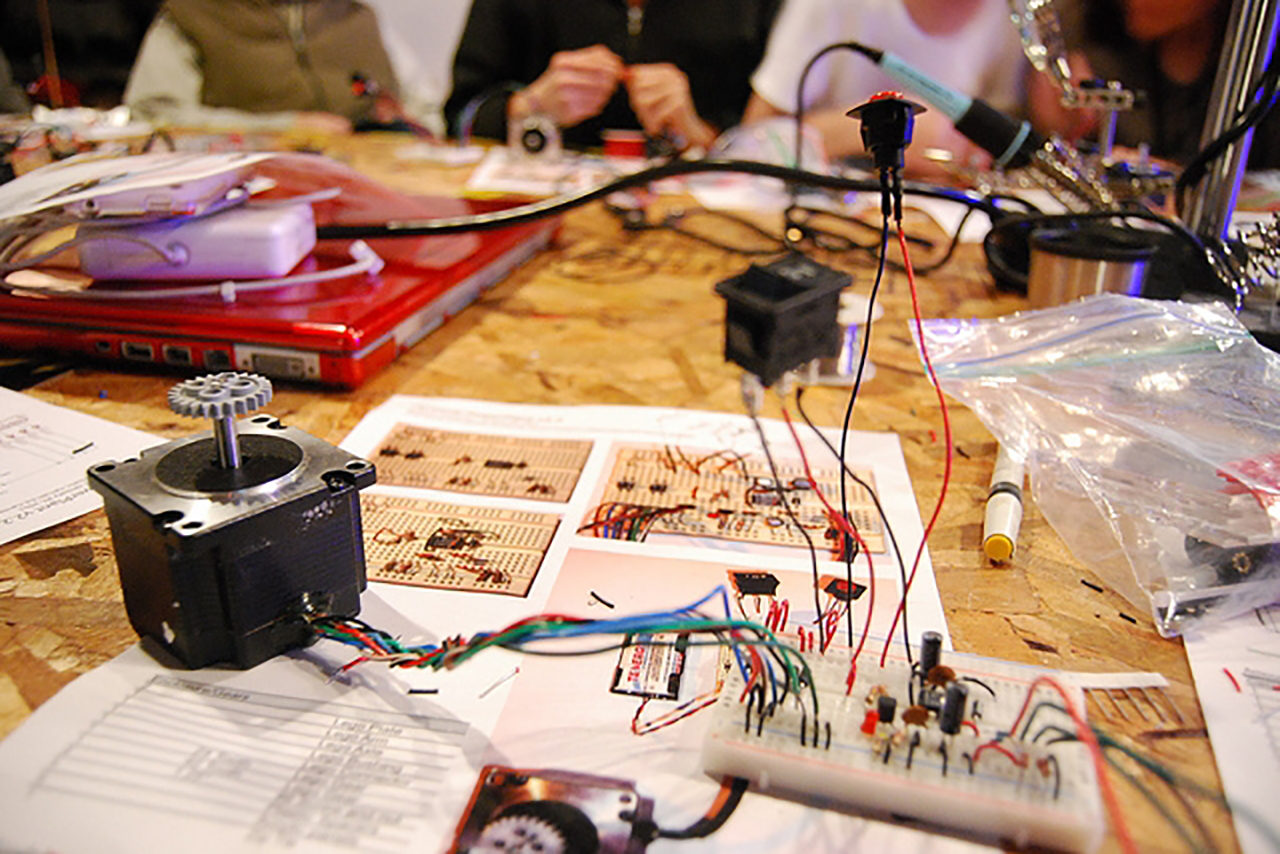 Hard-wood table with wires and other various tech tools.
