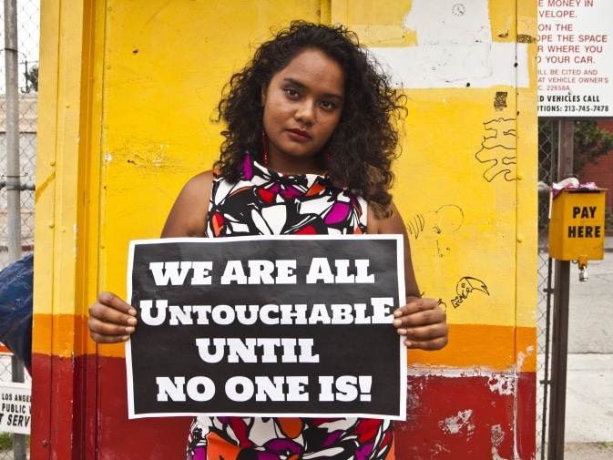 "Thenmozhi Soundararajan, winner of a 2017 Eyebeam Award, holding a sign saying ""We are all untouchable until no one is!"""
