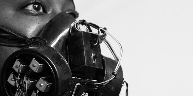 Black and white close-up of a person with a gas-mask-type contraption in front of a microphone.