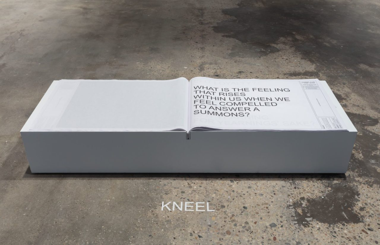 "A large-format book opened with large text giving directions for puppy-play sits atop a white pedestal. Before the pedestal it commands the viewer to ""kneel""."
