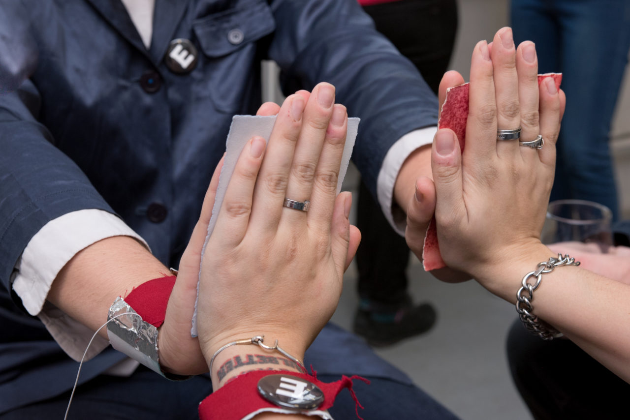 Two sets of hands join while touching