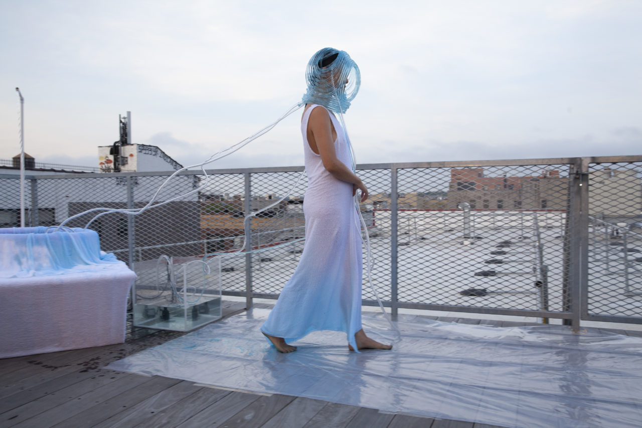 On a rooftop, a woman in an angelic dress gently steps forward, wearing an aquatic helmet connected to a water tank.
