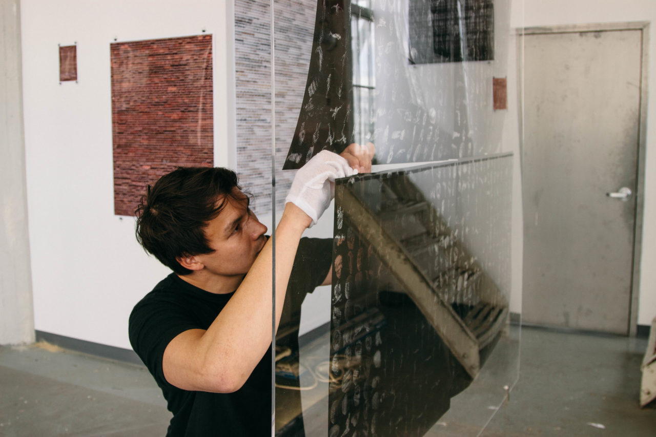 An artist making precise adjustments to their work in a glass case.