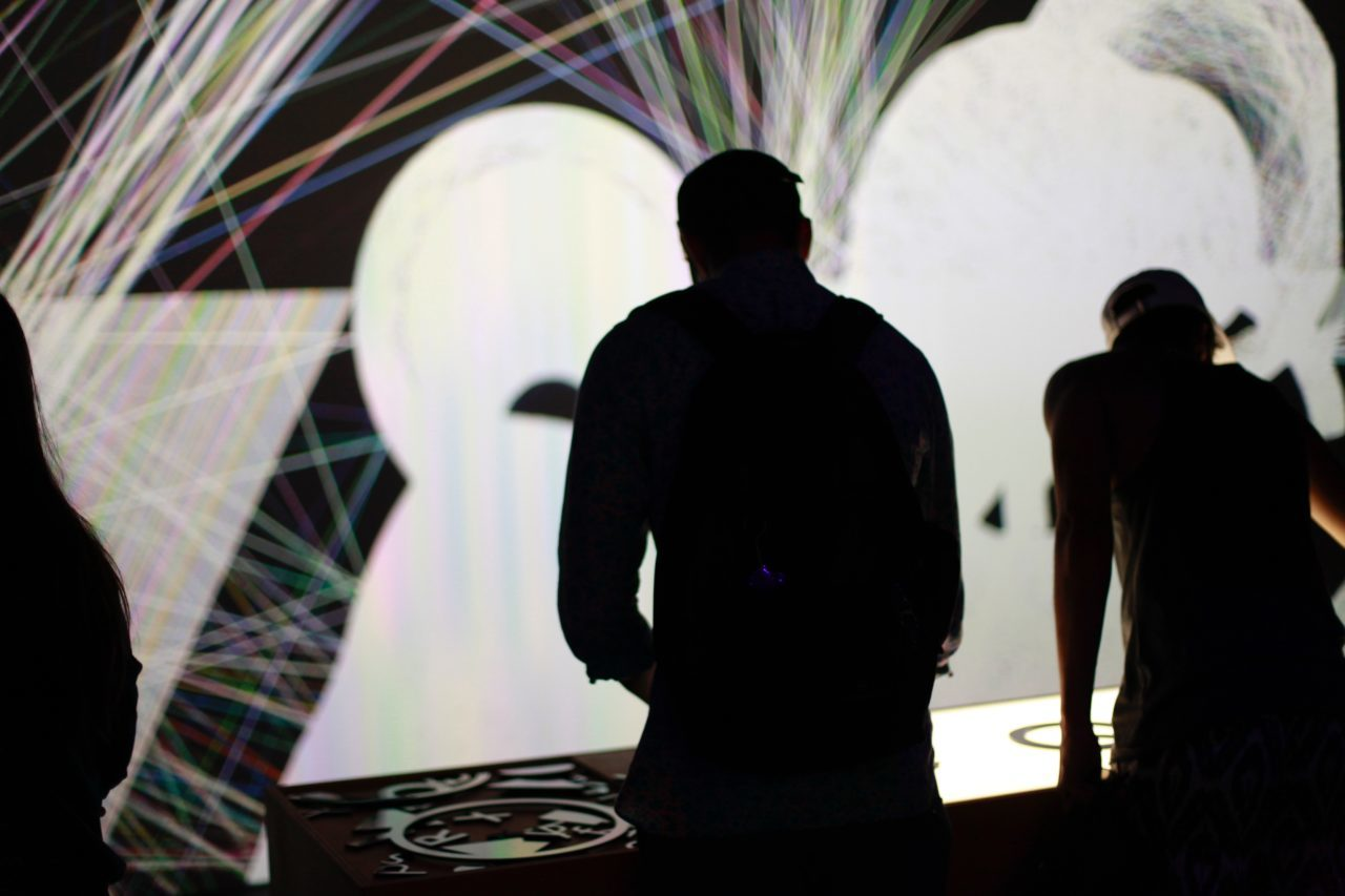 The silhouette of Zach Lieberman creating live projections of white shapes and colorful lines.