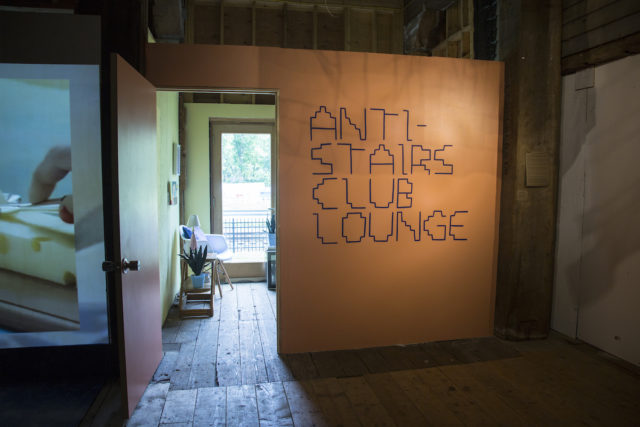 "An orange wall with big text in a stair-inspired font that says, ""Anti-Stairs Club Lounge."""