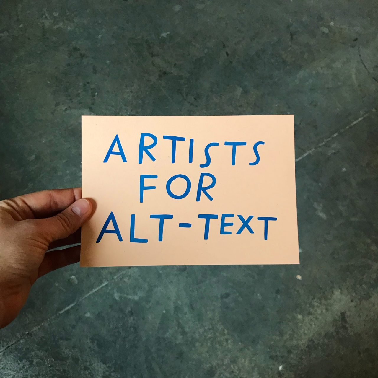 "A salmon-colored postcard with blue, uneven, handwritten capitals reading, ""Artists for Alt-Text"""
