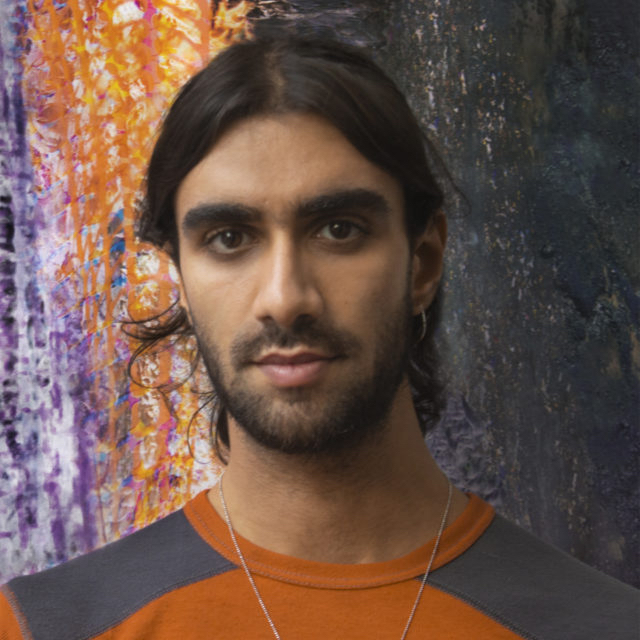 Portrait of young man with orange shirt and shoulder-length black hair, in front of a printed fire background. PC: Yusef Audeh