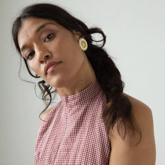 Pelenakeke stands head tilted at an angle looking directly to the camera wearing a gingham halter neck with her hair braided over one shoulder.