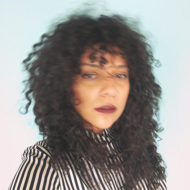Blurry image of an AfroCaribbean woman with long curly hair wearing a striped black and white button down shirt in front of a blown out turquoise / white background.