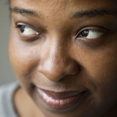 A close up image of young black woman with brown skin, brown eyes looks off camera. She is wearing a gray sweater.