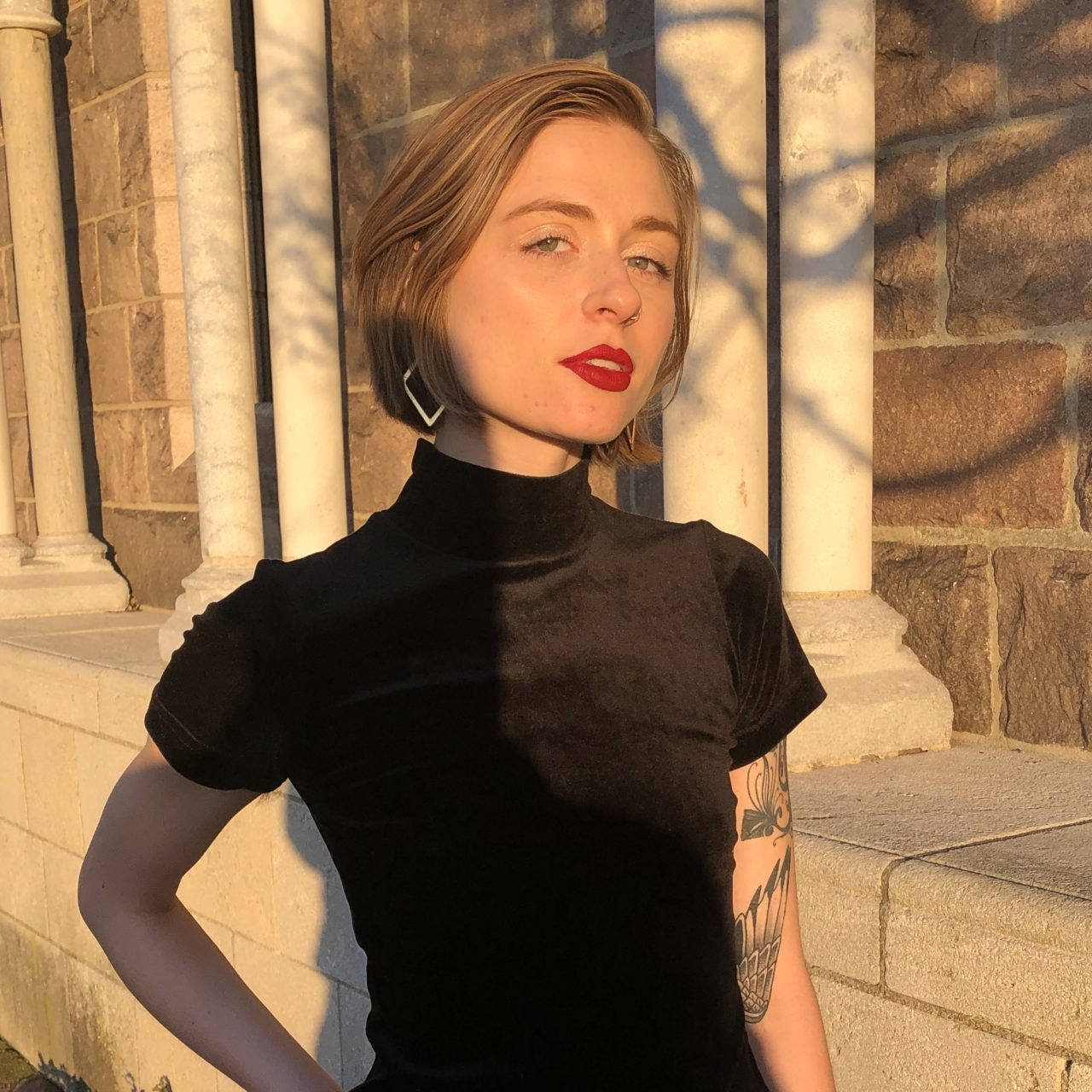 A young white femme with a short blond bob, and red lipstick looks directly into the camera. She is wearing a short-sleeved, black, velvet turtleneck and black leather pants. Her weight is planted on her right hip, where her right hand is also. She is standing in front of a medieval, stone building and you can nearly feel the desire emanating from her client (out of frame) who is taking the photo.