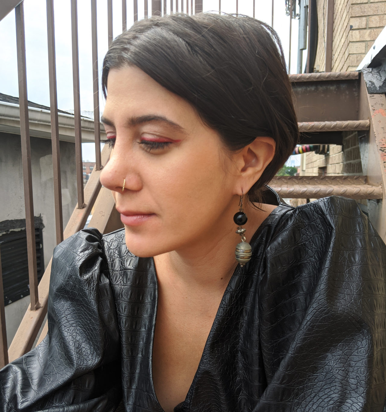 A profile image of a woman wearing black leather dress sitting on the staircase of a rooftop. She is wearing a red eyeliner and has a dark brown hair.