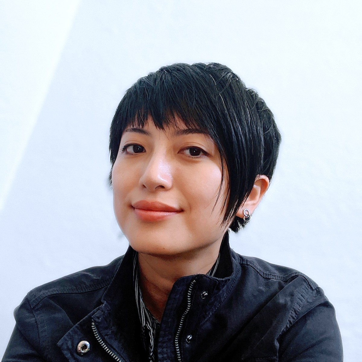 Photo of a non-binary Han Taiwanese descendent with a short, assymetrical haircut and a few strands of white hair. They have a diamond-shaped face, light-olive skin, almond-shaped eyes and a high nose bridge. They wear a black, unzipped jacket and a tiny earring consists of two intersecting rings. They appear to be sitting at the corner of the room and they look into the camera with a soft but confident expression.