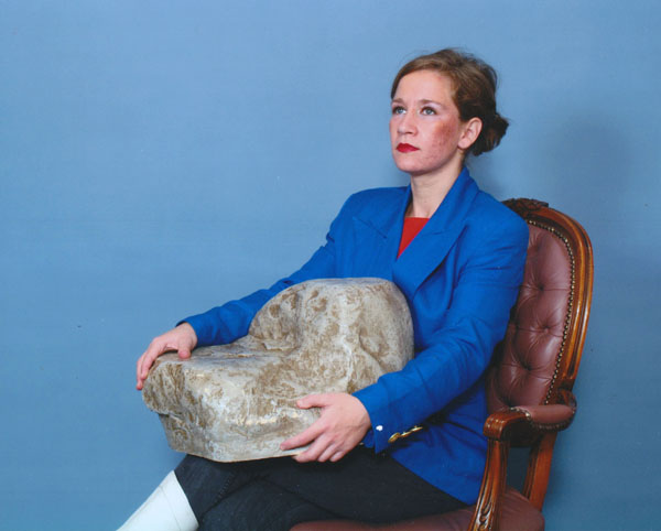 A young woman with fair skin sits in a 1970s Victorian Style chair, photographed in a portrait studio with bright lighting on an all blue background. Her light brown hair is pulled back into a bun and she is wearing heavy foundation and red lipstick. She is wearing a bright blue blazer and she clutches a rock that is almost as large as her, as she looks up.