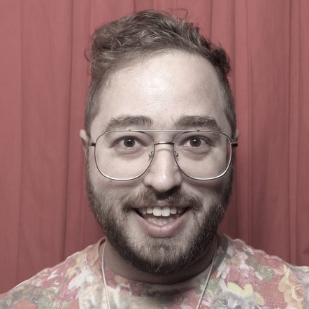 Harris in a photobooth with red backdrop. Harris is white with light brown hair, glasses, and facial hair, and is wearing a t-shirt with a collage of cats on it.
