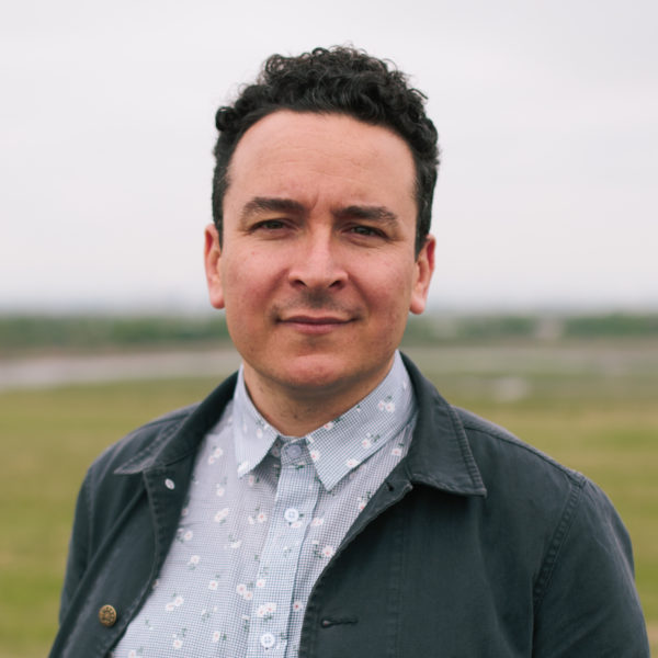 This is a headshot of Dylan Gauthier, an artist and curator, who presents as a white male with curly black hair, a sharp nose, and an uneven chin. He is wearing a black worker's shirt over a flower print white and black button-up shirt. The blurred background hints at a view of Freshkills Park, where the photo was taken. The photo was taken by Natalie Conn.