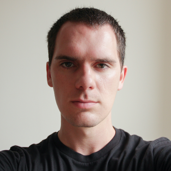Early 30s white male with very short brown hair, neutral face expression, clean shaven, black t-shirt.