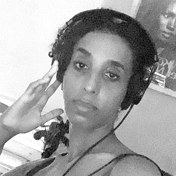 This is a black and white grainy photo of a close up of Rodan Tekle's face, she is a black woman with headphones on, one hand touching the headphone as she's looking straight into the camera with a serious but gentle gaze.