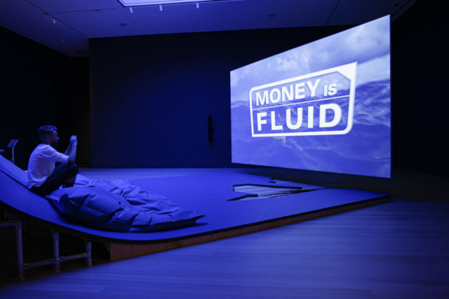 Photo from Hito Steyerl exhibition, lit in blue you see a screen that reads