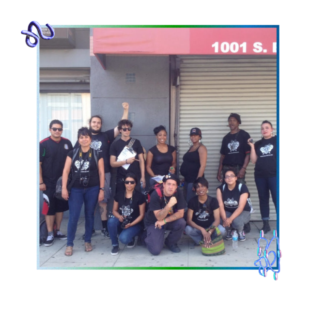 A predominantly BIPOC gathering of twelve adults smile as they stand and kneel on a sidewalk by a grey building in downtown Los Angeles. They are all dressed in black tops—many of which are a black t-shirt with a white screenprint of the Stop LAPD Spying Coalition logo—various dark-colored pants or shorts, and comfortable shoes. Four people are kneeling or squatting in the front row and eight people are standing in the back row. Some are wearing sunglasses, a hat, a backpack, or carrying a dSLR camera.