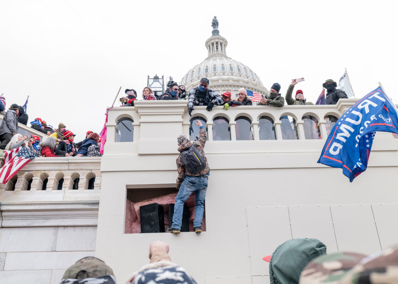 Man climbing the Capitol during the 2021 riot.