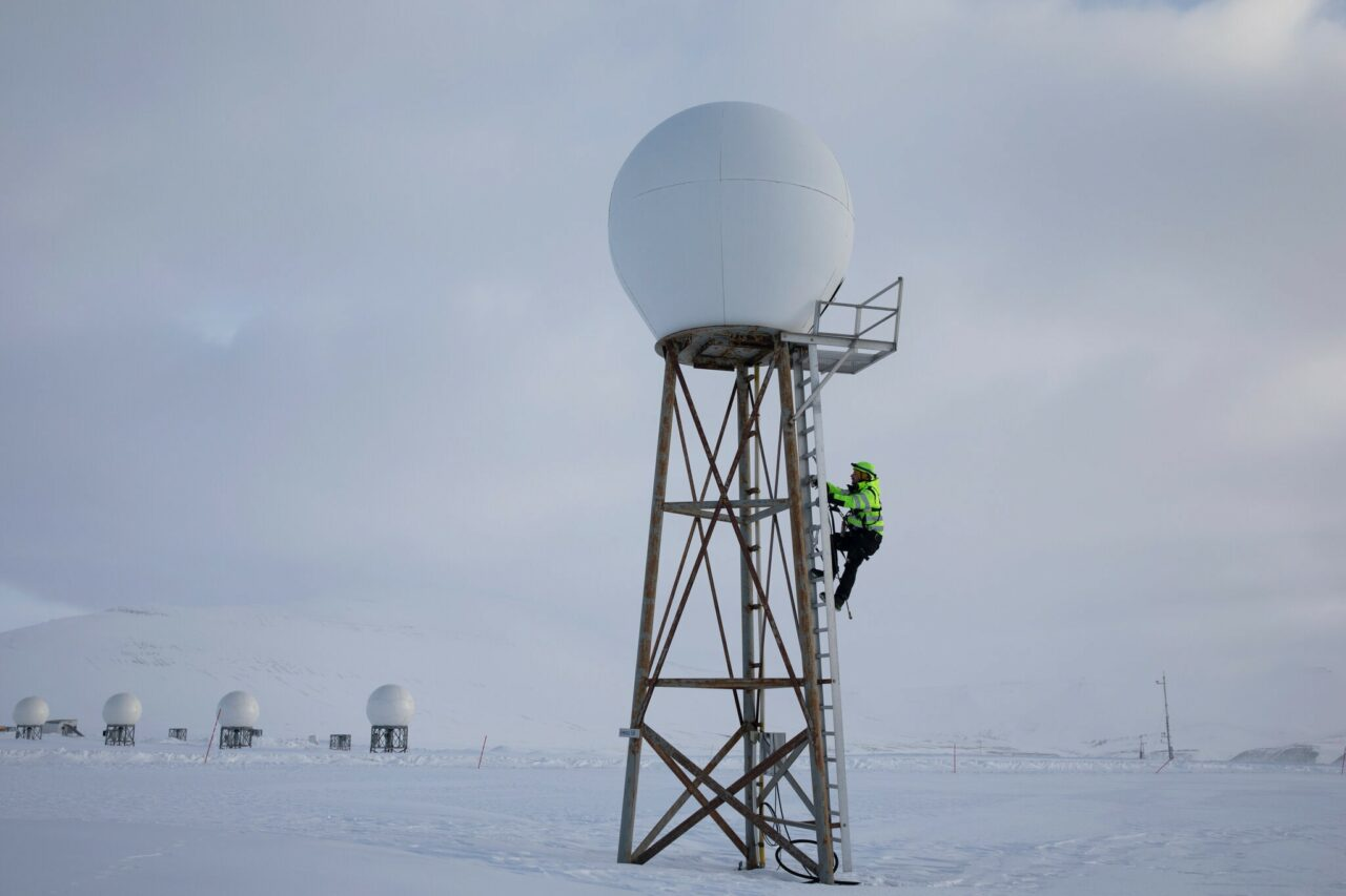 An engineer inspecting an antenna. The Arctic surrounds in white.